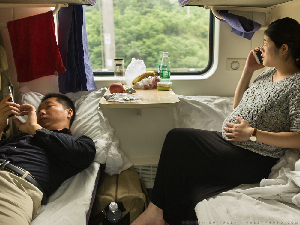 A pregnant woman from Gangu, talks to her mum while husband checks on his work. Between Tianshui and Longxi. Life in the sleeping compartments in the train from Guangzhou/Shenzhen to Xinjiang.