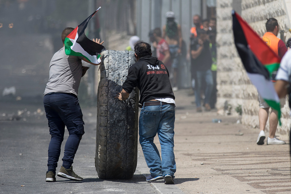 Bethlehem, Palestine. 15 May 2018. Protesters move a tyre to a barricade during clashes with Israeli soldiers on the 70th anniversary of the Nakba (Catastrophe) when over 700,000 Palestinians were forcibly moved from their homes during the creation of Israel. © Craig Redmond