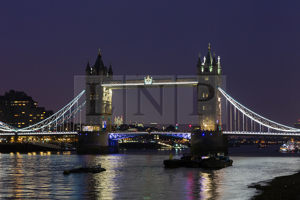 © Licensed to London News Pictures. 23/03/2016. London, UK. Tower Bridge is dimmed in black, one of the colours of the Belgian tricolor flag this evening, in a tribute to victims of the Belgium terrorist attacks which took place yesterday. Landmarks across London are paying tribute this evening. Photo credit : Vickie Flores/LNP