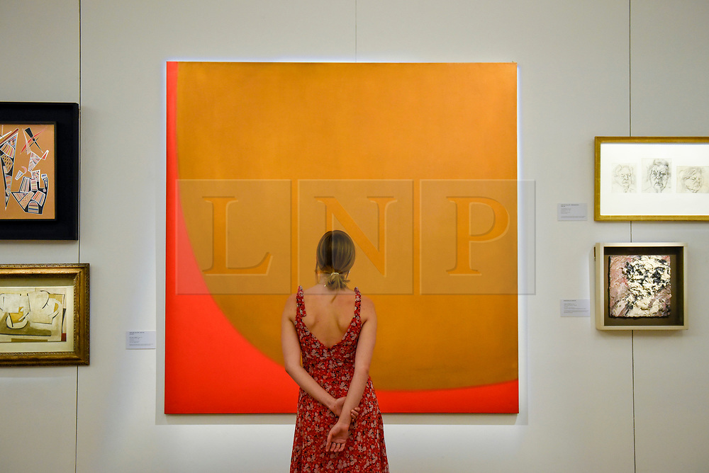 """© Licensed to London News Pictures. 17/07/2019. LONDON, UK. A staff member views """"9-1960 (Red Off Cut"""", 1960, by William Turnbull at the preview of """"Brave New Visions: The Émigrés who transformed the British Art World"""", a new exhibition at Sotheby's gallery in New Bond Street which runs 17 July to 9 August 2019.  The show is also part of """"Insiders / Outsiders"""", a nationwide, year long festival celebrating refugees from Nazi Europe and their contribution to British culture.  Photo credit: Stephen Chung/LNP"""