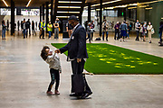 Ben Okri dancing with his daughter Mirabella, 'Can't you hear the future weeping? Our love must save the world' is a statement by the writer Ben Okri which was revealed in a live art piece by eco Artists Ackroyd & Harvey on 25th July 2021 in the Turbine Hall of Tate Modern, London, United Kingdom. Conceived as a message to us all, the artists were calling yet again for us to act in the face of our climate crisis. In the temporary 'greenhouse' of Tate, the seeds burst into life with the added dimension of Okri's clarion call to use active love to inspire the change we need. Stencilled letters, blocking the light, then removed, created the message within the grass. For the final act, in a solemn ritual, the grass banner was rolled up, carried out by volunteer performers and floated on the Thames. Visible from up high, floating on the tidal river, the luminescent yellow letters stood out boldly from the rich green of the grass. At the end of the day the banner was dismantled and the grass art distributed to anyone who wanted to continue to grow the words.