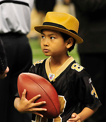 Jan 16, 2010 - New Orleans, Louisiana, USA - MADDOX plays with a football the the Saints gave him before the NFC playoff game.Actor Brad Pitt and his adopted son Maddox, Maddox looks at Brads blackberry after Brad took his photo and then they sent it to his mom Angelina Jolie while on the sidelines before teh game. walk on the New Orleans Saints side line before the NFC playoff game between the Saints and the Cardinals Saturday in Louisiana at the SuperDome. Brad has been instrumental in rebuilding the lower ninth ward in New Orleans through his Make it Right non profit that is building ''green homes'' where Hurricane Katrina destroyed everything. The Saints beat the Cardinals to advance in the playoffs. Photo ©Suzi Altman/Suzisnaps.comNFL Saints -Cardinals playoffs. (Credit Image: © Suzi Altman/ZUMA Press)