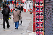 Elderly man wearing a face mask walks past shuttered closed shops covered with Union Jack flags along the shopping district Oxford Street which is largely empty of shoppers as the national coronavirus lockdown three continues on 28th January 2021 in London, United Kingdom. Following the surge in cases over the Winter including a new UK variant of Covid-19, this nationwide lockdown advises all citizens to follow the message to stay at home, protect the NHS and save lives.