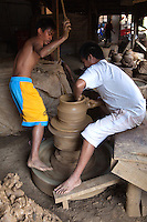 Filipino potters turning the pottery wheel manually - Burnay is a type of earthenware crafted by a potter's hands with the aid of a potter's wheel using sand for tempering and is fired at a high temperature in huge  kilns that makes it more durable than other terra cotta. It is said that the burnay technique was brought to Vigan by Chinese artisans.