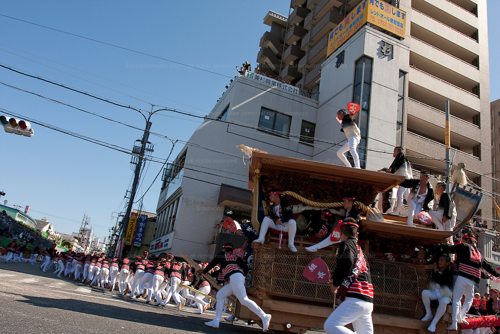 Ornately carved floats called Danjiri are pulled through the streets of Kishiwada during the danjiri festival or matsuri. Each float weigh about 4 tonnes and stands over 3 metres high. They are pulled by teams of up to a thousand people, young and old, and each challenges itself to skid the danjiri round street corners at great speed. Kishiwada, Osaka, Japan Sunday, September 20th 2009