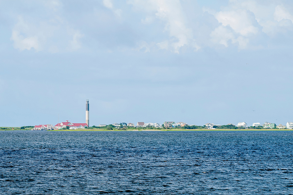 View of the Oak Island Lighthouse from the fishing pier in Southport, North Carolina on Saturday, August 7, 2021. Copyright 2021 Jason Barnette