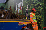 With a background of a fantasy garden hanging hoarding media, a workman organises delivery of construction materials on the back of a lorry, to a Dior shop being refurbished on Bond Street in central London. Resting between tasks, the man has his hands in pockets, wearing hi-visiblity clothing and safety helmet. Steel struts for reinforced concrete are awaiting lifting from the truck. The Dior store occupies a prime location on one of London's most prestigious streets known for fashion and jewellery and work continues behind the screen, hidden to passers-by.