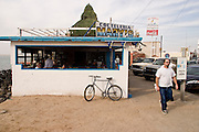 "15 FEBRUARY 2003 - PUERTO PENASCO, SONORA, MEXICO: A tourist walks past a seafood restaurant on the ""Malecon,"" (seafront boulevard) in Puerto Penasco, Sonora, Mexico. Puerto Penasco is known as Rocky Point among visitors to the Mexican beach town on the Sea of Cortez. The area is famous for wide beaches and fresh seafood, especially shellfish.   PHOTO BY JACK KURTZ"