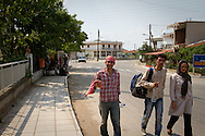 Afghan and Pakistani migrants walk through a border town early in the morning en route to handing themselves into the Greek authorities. Migrants look for the police in order to become registered on the EU database.