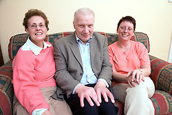 Older couple with their daughter sitting on the sofa,