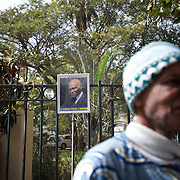 February 22, 2012 - Dakar, Senegal: A local man passes by a campaign poster of the president Abdoulaye Wade is displayed in the fence of the senate's building in central Dakar, ahead of the presidential elections on the 26th of February. (Paulo Nunes dos Santos/Polaris)