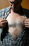 male person opening shirt and looking at his breast hair