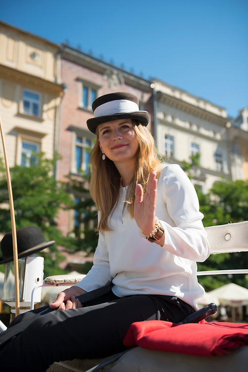 Krakow, Poland - August 26, 2016: A Polish woman sits in her horse-drawn carriage in Krakow's Rynek Glowny square, waiting for a fare. The carriages are popular with tourists.