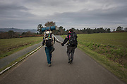 Pilgrims Giulia Borsci, 33, from Italy (right) and Victor Bezerra, 25, from Brazil, hold hands during their four months journey on foot from Italy, following the Way of St. James, or El Camino de Santiago, a network of ancient pilgrim routes stretching across Europe and converging at the tomb of St. James (Santiago in Spanish) in Santiago de Campostela in northwest Spain, on November 24, 2020 close to Ligonde, Galicia, Spain. The Camino de Santiago is being affected by Covid-19 with strict restrictions regarding services and mobility along the routes. Starting October 30, 2020, Spanish authorities closed among others, the  perimeter of Santiago de Compostela. Only pilgrims that have been journeying before October 30 can stop at the cathedral of Santiago de Campostela, but they are not allowed to stay overnight and have to transit through.