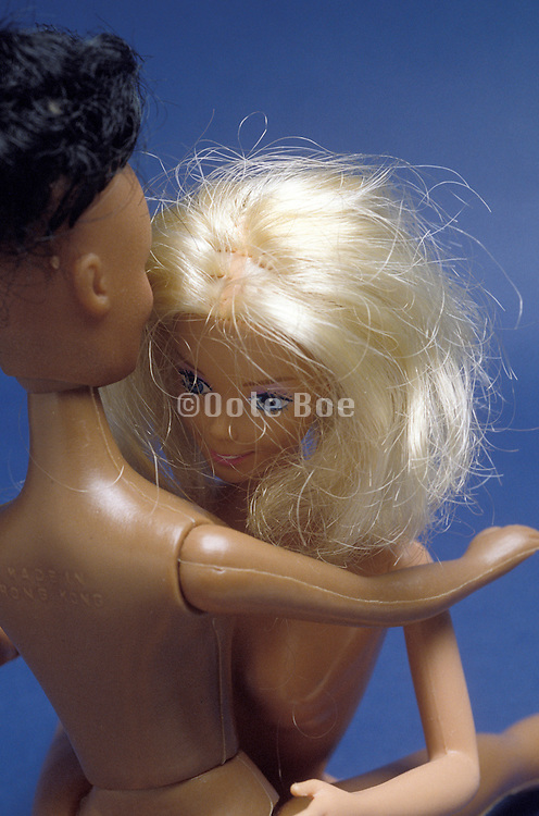 Two nude Barbie dolls embracing each other