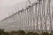 Wind farm producing electricity at San Gorgonio Pass, near Palm Springs, California. Wind Turbines. View of a wind farm with several wind turbines each with 3 spinning rotor blades. Wind power is used to drive a turbine for the generation of electricity. The electrical energy produced from a turbine is proportional to the cube of the wind speed. Thus, a 10-meter per second wind will produce 8 times more energy than a 5 meter per second wind. Wind turbines vary in size from large generators with a 1-3 megawatt capacity to small machines producing only a few kilowatts. (1986).