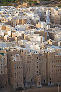 "An aerial view of the town of Shibam, in the Hadhramawt Valley, Yemen. Shibam is a World Heritage Site. The old walled city with it's talk mud brick buildings has been called 'the Manhattan of the desert""."