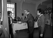 Scout Inducted Using Sign Language.   (P6)..1981..08.12.1981..12.08.1981..8th December 1981..Joe Needham, a deaf and dumb resident in Stewart's Hospital, Palmerstown, Co Dublin was enrolled into the 43rd Dublin (Palmerstown) unit of the Scouting Association of Ireland. The Chief Scout, Mr Joe McGough carried out the enrollment at the hospital. Ms Domenica Malocca, a teacher in the class for the deaf at the hospital, translated the Scout Promise into sign language during the ceremony...A new recruit is congratulated by the Chief Scout, Mr Joe McGough and Estelle Feldman, Scout Leader, 43rd Dublin unit.