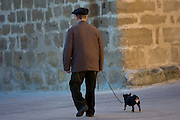 Old man walking his chihuahua dog in the streets of Laguardia, Northern Spain..