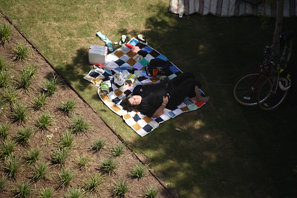 Stock photo of a woman napping on a picnic blanket in the shade after a picnic in the park