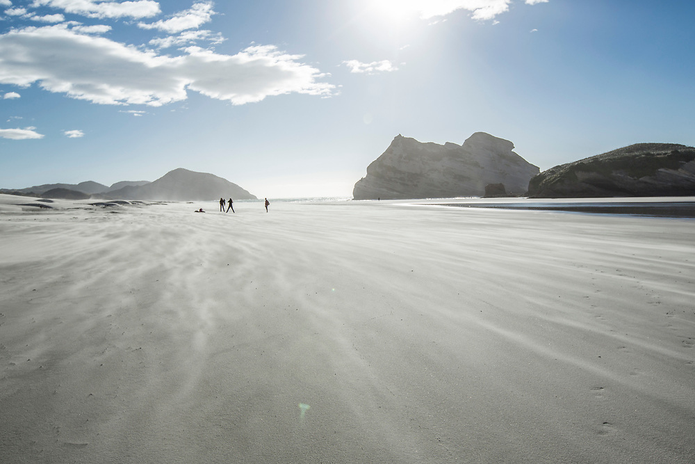 Distant people on the windswept spectacular Wharaiki Beach, Golden Bay, Nelson