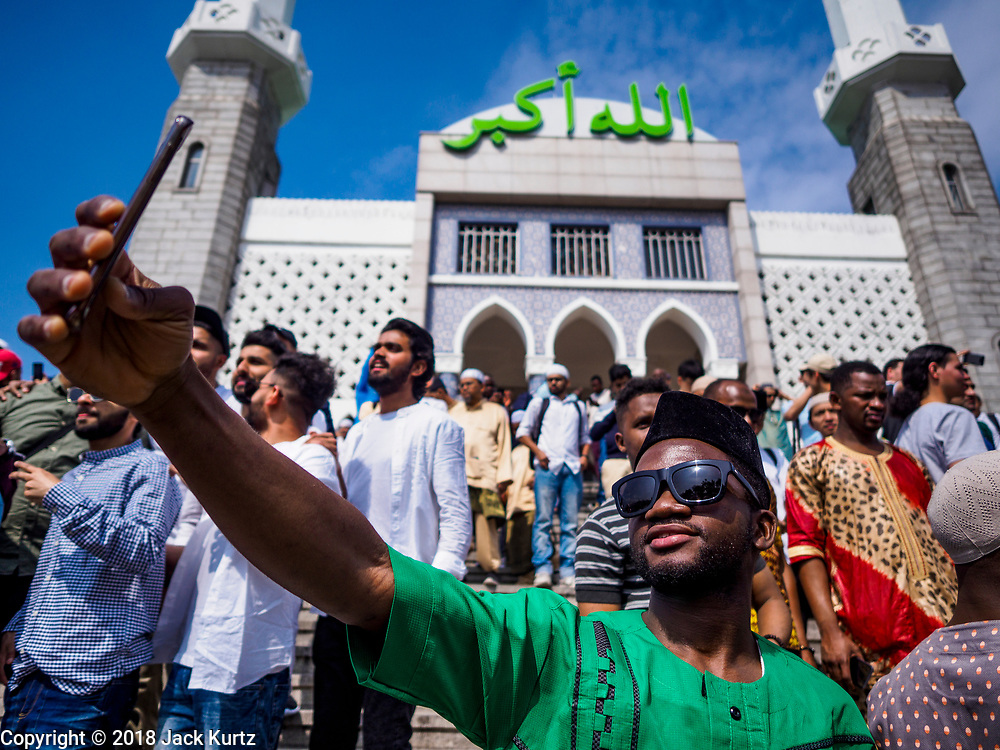 """15 JUNE 2018 - SEOUL, SOUTH KOREA: A Muslim African worker in Seoul takes a """"selfie"""" with a smart phone at Seoul Central Mosque on Eid al Fitr, the Muslim Holy Day that marks the end of the Holy Month of Ramadan. There are fewer than 100,000 Korean Muslims, but there is a large community of Muslim immigrants in South Korea, most in Seoul. Thousands of people attend Eid services at Seoul Central Mosque, the largest mosque in South Korea.   PHOTO BY JACK KURTZ"""