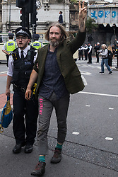 Metropolitan Police officers arrest an environmental activist from Extinction Rebellion after a vintage bus was used as base to block a road junction to the south of London Bridge on the ninth day of Impossible Rebellion protests on 31st August 2021 in London, United Kingdom. Extinction Rebellion are calling on the UK government to cease all new fossil fuel investment with immediate effect.