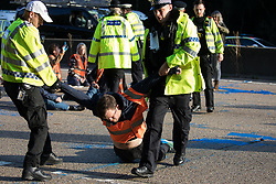 Ockham, UK. 21st September, 2021. Surrey Police officers remove Insulate Britain climate activists from the clockwise carriageway of the M25 between Junctions 9 and 10 where they had been protesting as part of a campaign intended to push the UK government to make significant legislative change to start lowering emissions. Both carriageways were briefly blocked before being cleared by Surrey Police. The activists are demanding that the government immediately promises both to fully fund and ensure the insulation of all social housing in Britain by 2025 and to produce within four months a legally binding national plan to fully fund and ensure the full low-energy and low-carbon whole-house retrofit, with no externalised costs, of all homes in Britain by 2030.