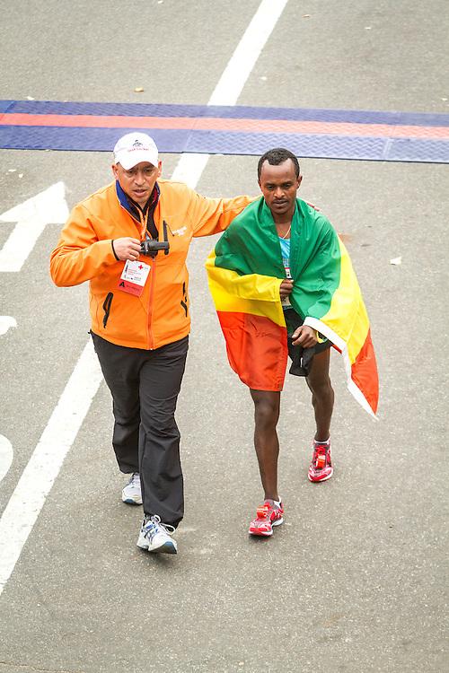 ING New York CIty Marathon: runner-up Tsegaye Kebede with Ethipoian flag escorted near finish line by race official