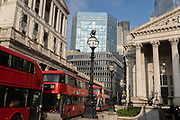 Days before the Chancellor Rishi Sunak delivers his Budget, buses queue at red lights with a wide view of the Bank of England left and Royal Exchange right in the City of London, the capitals financial district, on 1st March 2021, in London, England.