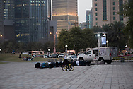 A group of men pray near sunset on the Corniche in Doha, Qatar. A mobile mosque is parked beside them.