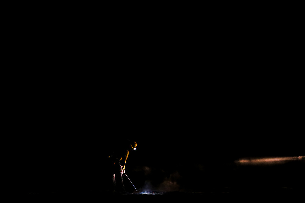 A firefighter works to extinguish hot spots after midnight following a fire that broke out along Highway 166 west of New Cuyama, California, Sunday, August 6, 2017. The fire reported around 9:30 p.m. Saturday night, Aug. 5, burned nearly 30 acres according to the Santa Barbara County Fire Department.