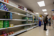 A masked shopper walks the aisles of British supermarket chain Tesco as rows of shelves are left empty amidst nationwide labour shortages on 4th September, 2021 in Leeds, United Kingdom. A combination of Brexit and Covid-19 is reportedly exacerbating an already severe staff shortage in the British workforce, with a lack of HGV drivers leading to empty shelves in supermarkets up and down the country.