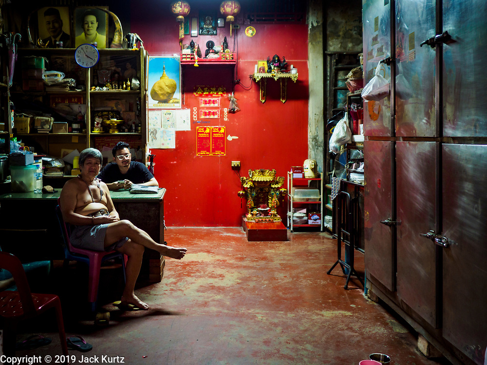 """26 FEBRUARY 2019 - BANGKOK, THAILAND: Men in their shophouse in a market in Bangkok's Chinatown. Bangkok has one of the largest """"Chinatown"""" districts in the world. About 14% of all Thais have some Chinese ancestry and Chinese cultural practices are incorporated in many facets of Thai daily life.       PHOTO BY JACK KURTZ"""