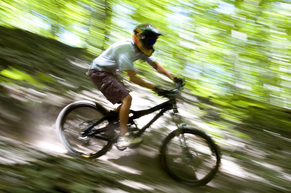 A mountain biker blurs through the woods while freeriding near Marquette. Michigan.