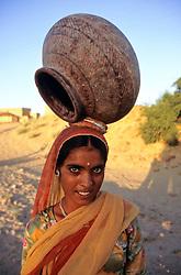 Asia, India, Rajasthan, Jaisalmer. Hindu woman carries clay water vessel to Lodurva village well (MR).