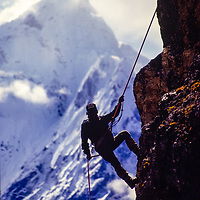 Pertemba Sherpa demonstrates rappelling to his colleagues at an early mountaineering school for sherpas in the Khumbu region of Nepal, 1980.Mt. Ama Dablam bkg.