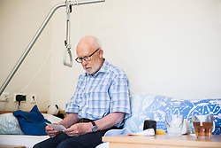 Senior man reading something while sitting on his bed in rest home, Bavaria, Germany, Europe
