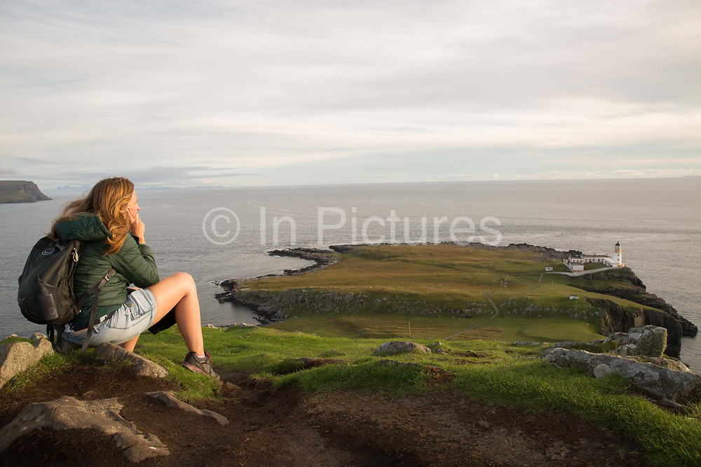 A woman overlooking Neist Point lighthouse in Glendale on the 4th September 2016 on the Isle of Skye in Scotland in the United Kingdom. Neist Point is the most Westerly point on the Isle of Skye with views over Moonen Bay to Waterstein Head.