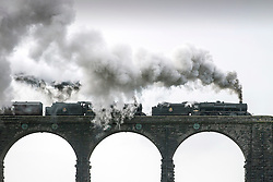 © Licensed to London News Pictures. 07/07/2016. Ingleton UK. File picture taken 23/01/2016 shows a train passing over Ribblehead Viaduct. After heavy rainfall in February caused a 500,000 ton land slip on the Settle to Carlisle railway which includes the world famous Ribblehead Viaduct the line has been partly closed, now a £23M repair project will see hundreds of concrete filled steel tubes set into the hillside to form a corridor on which a 100 metre long concrete slab will be placed to give the railway a solid base and the line will be fully re-opened next year. Photo credit: Andrew McCaren/LNP