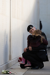 A veteran comforts a girl at the National Memorial Arboretum, Alrewas, Staffordshire, on the 100th anniversary of the signing of the Armistice which marked the end of the First World War.