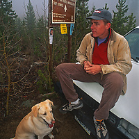 Steve Bechtel and his dog stand vigil during the search for his wife Amy, who disappeared while running along this lonely road above Lander, Wyoming.
