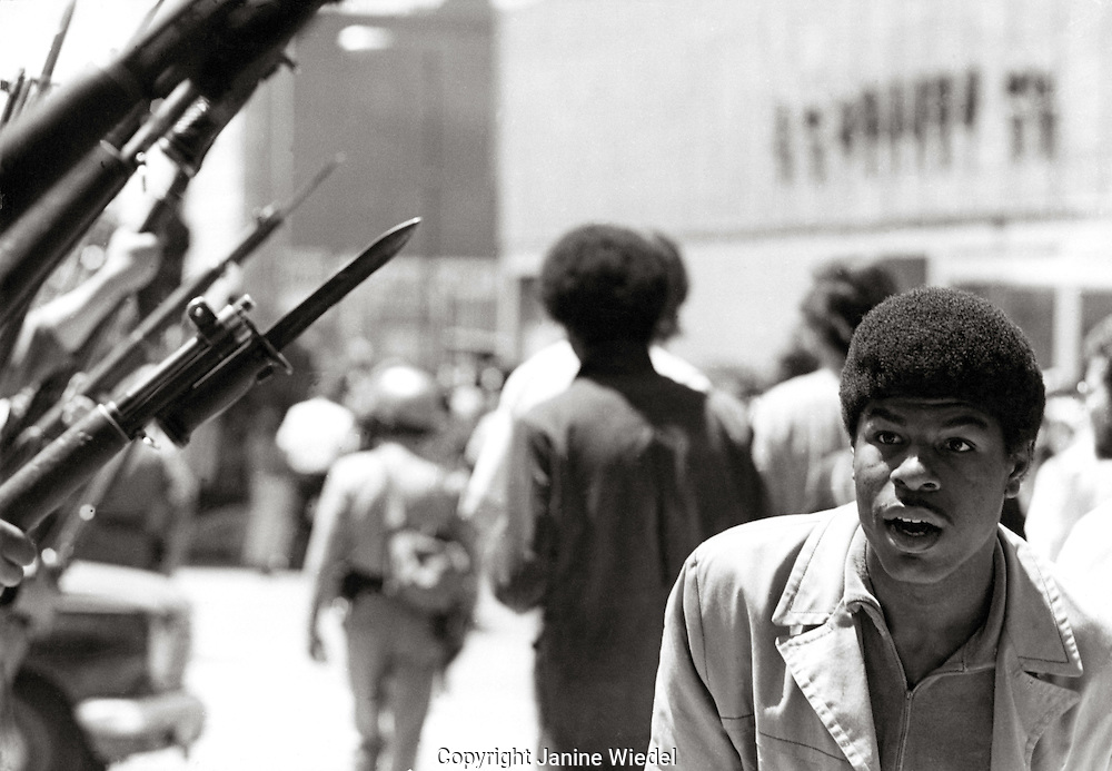 Young man passes national guard's rifles during aftermath of riots in Berkley California, 1969