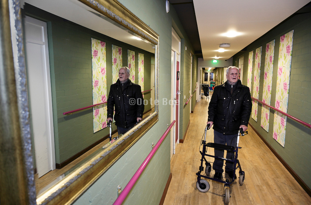 senior man with walker in the hallway of a retirement home for the elderly