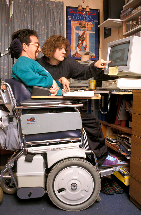 Disabled man working on his computer in residential home,