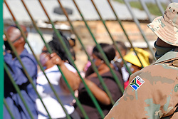 JOHANNESBURG, SOUTH AFRICA - MAY 08: An SANDF member watches people gathering at a food distribution centre in Diepsloot on May 08, 2020 in Diepsloot, South Africa. In partnership with with government and Celebration Church, Engen Fuel Retailers contributed food parcels for over 4000 familes in Diepsloot during lockdown level 4. (Photo by Dino Lloyd)