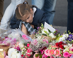Parliament Square, Westminster, London, June 17th 2016. Following the murder of Jo Cox MP a vigil is held as friends and members of the public lay flowers, light candles and leave notes of condolence and love in Parliament Square, opposite the House of Commons. PICTURED: A girl has a moment of quiet contemplation
