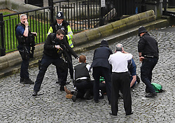 NOTE ALTERNATE CROP A policeman points a gun at a man on the floor as emergency services attend the scene outside the Palace of Westminster, London, after policeman has been stabbed and his apparent attacker shot by officers in a major security incident at the Houses of Parliament.