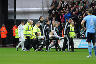 Swansea city's Chico Flores is stretchered off injured in the 1st half. Barclays Premier league, Swansea city v Queens Park Rangers at the Liberty Stadium in Swansea, South Wales on Saturday  9th Feb 2013. pic by Andrew Orchard, Andrew Orchard sports photography,