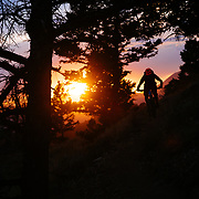 Andrew Whiteford silhouetted at sunset with a trail glowing from dust billowing from his speed.